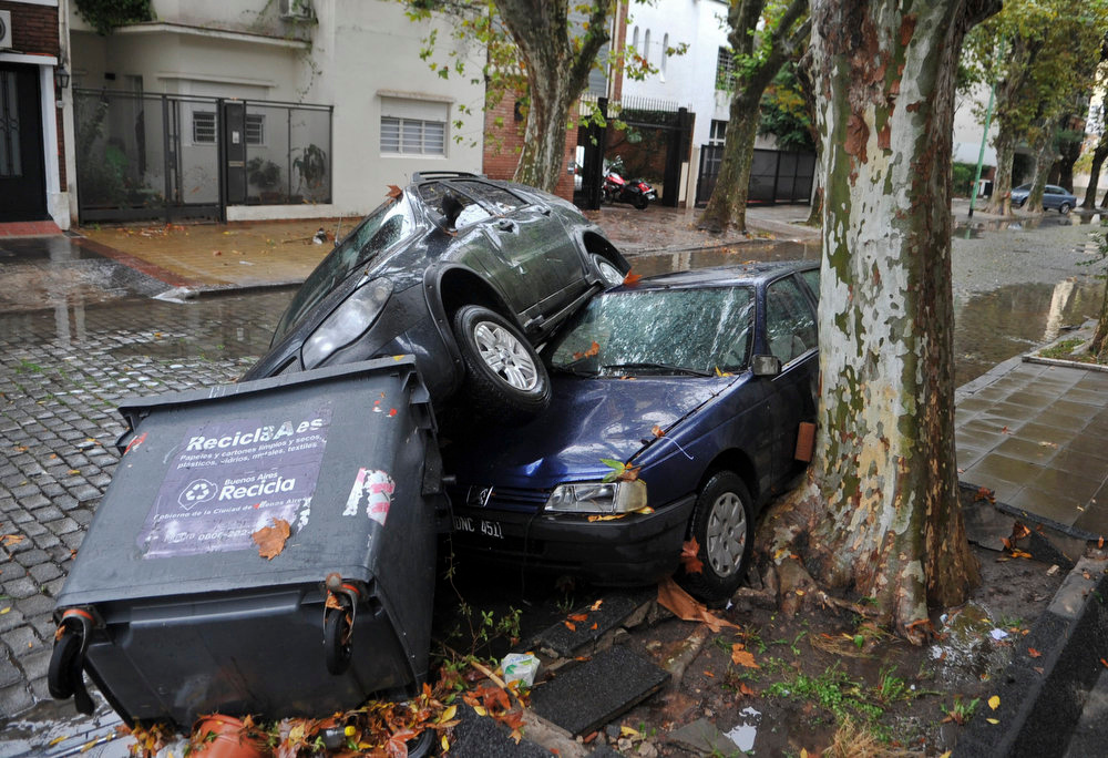 . Cars and garbage containers lay piled up after flash flooding caused damage overnight in Buenos Aires, Argentina, Tuesday, April 2, 2013. According to city officials, at least five people were killed during the heavy rains. (AP Photo/Leonardo Zavattaro, Telam)