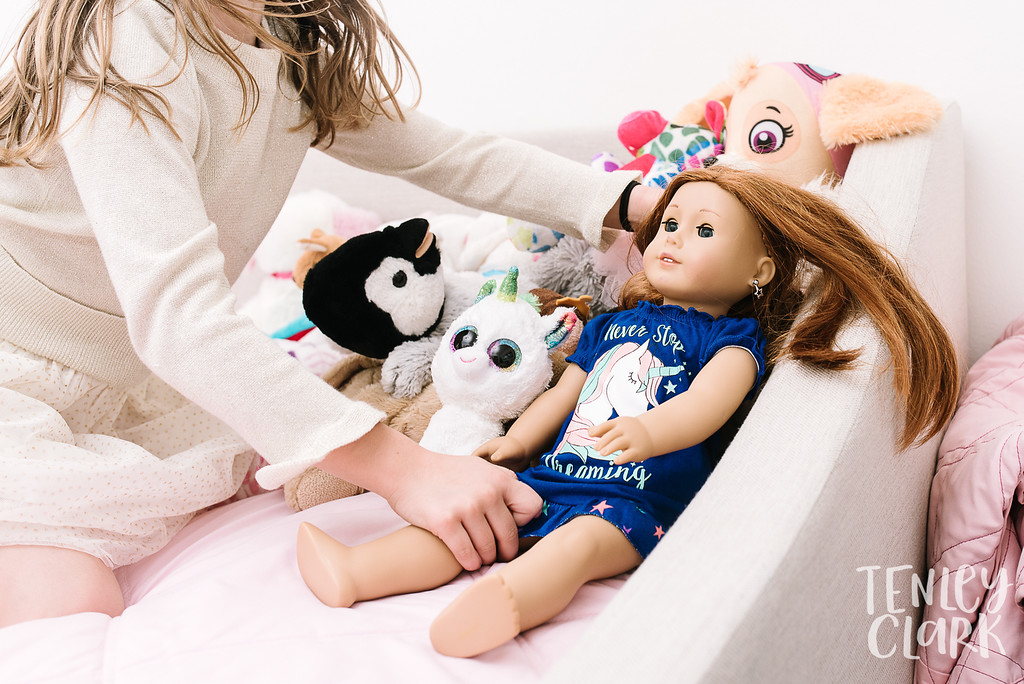 Little girl grabbing American Girl doll. Lifestyle in-home family photoshoot in Marin, CA by Tenley Clark Photography.