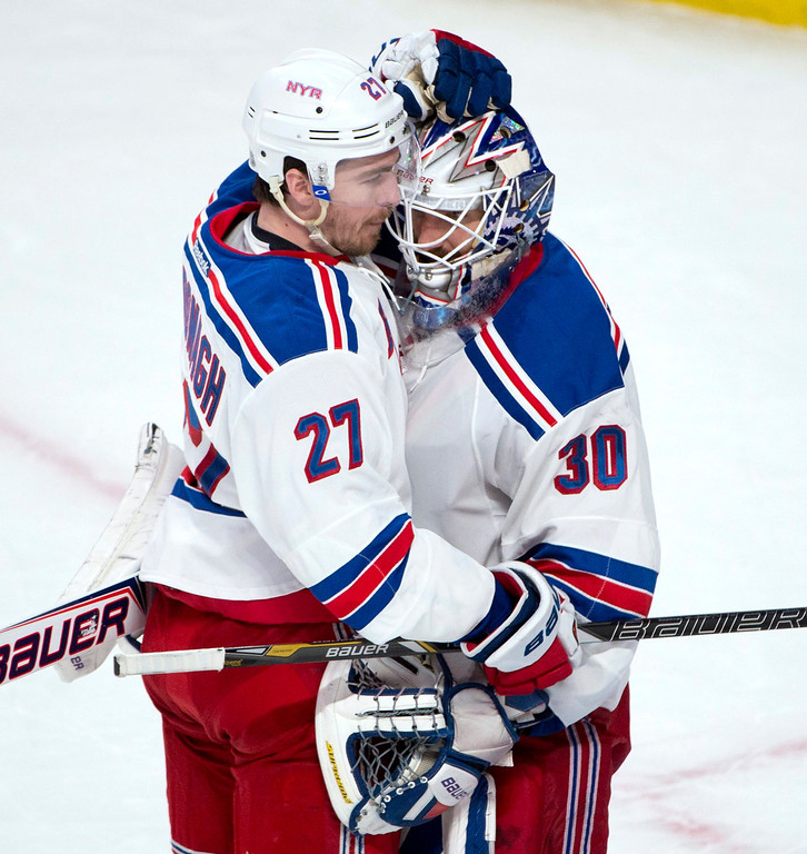 . New York Rangers defenseman Ryan McDonagh, left, embraces goalie Henrik Lundqvist after their 7-2 win over the Montreal Canadiens in Game 1 of the Eastern Conference finals in the NHL hockey Stanley Cup playoffs in Montreal on Saturday, May 17, 2014. (AP Photo/The Canadian Press, Adrian Wyld)
