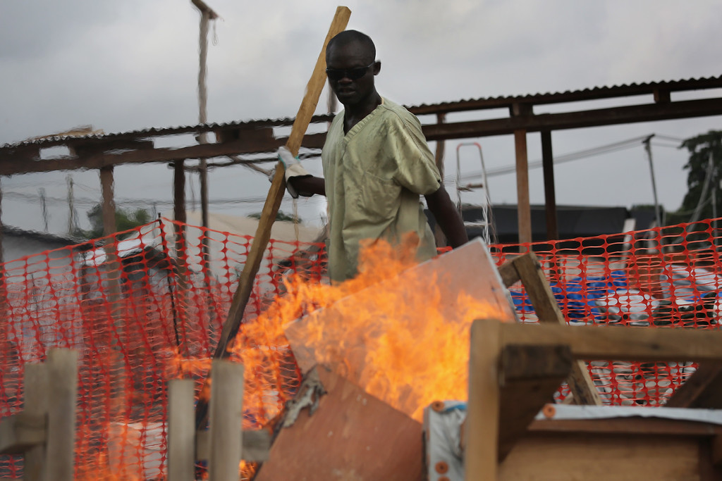 . A health worker from Doctors Without Borders (MSF), lights fire to materiel from from the Ebola Treatment Unit (ETU), on January 26, 2015 in Paynesville, Liberia. MSF, one of the first aid organizations to respond to the Ebola epidemic in Liberia, is destroying much of the ELWA 3 high-risk treatment area, reducing from 250 to 30 beds, in light of recent gains in eradicating the disease. In addition, other aid organizations have built ETUs, creating excess bed space for Ebola victims in and around the capital of Monrovia.  (Photo by John Moore/Getty Images)