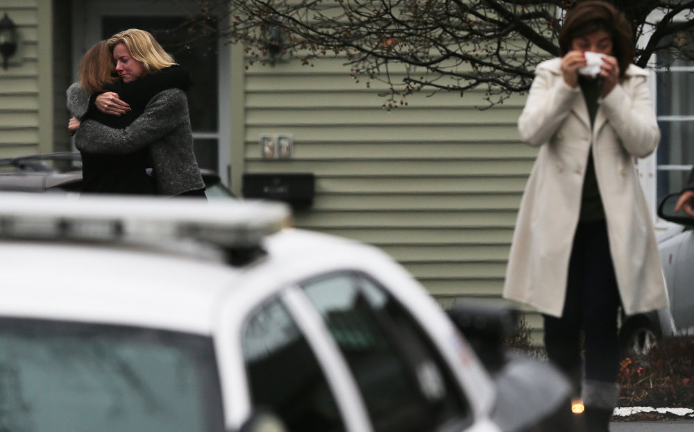 Description of . Mourners embrace while deparing Honan Funeral Home after the funeral for six-year-old Jack Pinto on December 17, 2012 in Newtown Connecticut. Pinto was one of the 20 students killed in the Sandy Hook Elementary School mass shooting.  (Photo by Mario Tama/Getty Images)