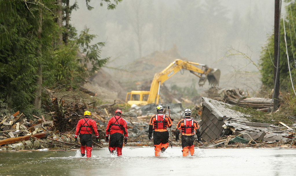 . Four search and rescue workers wade through water covering Washington Highway 530 Thursday, March 27, 2014, on the eastern edge of the massive mudslide that struck Saturday near Darrington, Wash. as heavy equipment moves trees and other debris in the background. (AP Photo/Ted S. Warren, Pool)