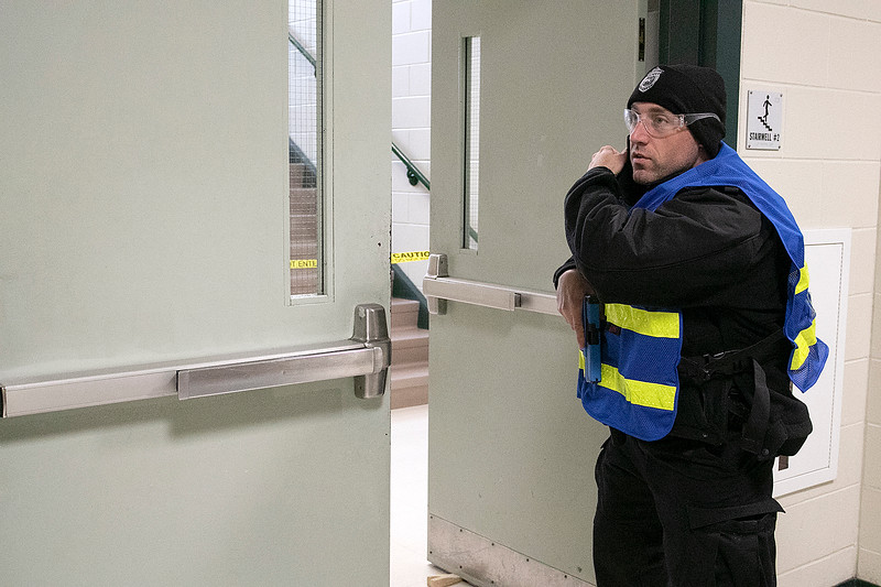 Police and firefighers from many Massachusetts departments participated in the the AAIR, Active Attack Integrated Response, class put on by ALERRT, Advanced Law Enforcement Rapid Response Training, at Sky View Middle School on Tuesday, Feb. 18, 2020. Waltham Officer Nick Zagami talk to headquarters as he guards on of the entry ways during one of the scenarios. SENTINEL & ENTERPRISE/JOHN LOVE