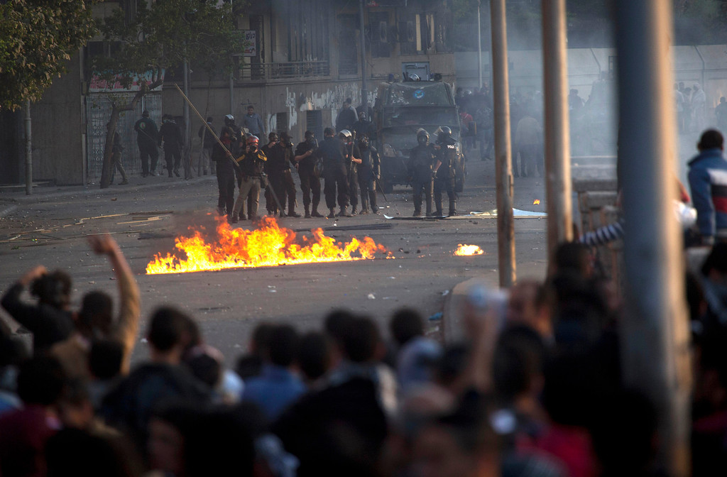 . Egyptian protesters clash with riot police in downtown Cairo, Egypt, Saturday, March 9, 2013. Security officials say a protester has died during clashes between police and hundreds of stone-throwing demonstrators in central Cairo. The officials say the protester died Saturday on a Nile-side road where clashes have been taking place daily between anti-government protesters and police near two luxury hotels and the U.S. and British embassies. (AP Photo/Nasser Nasser)