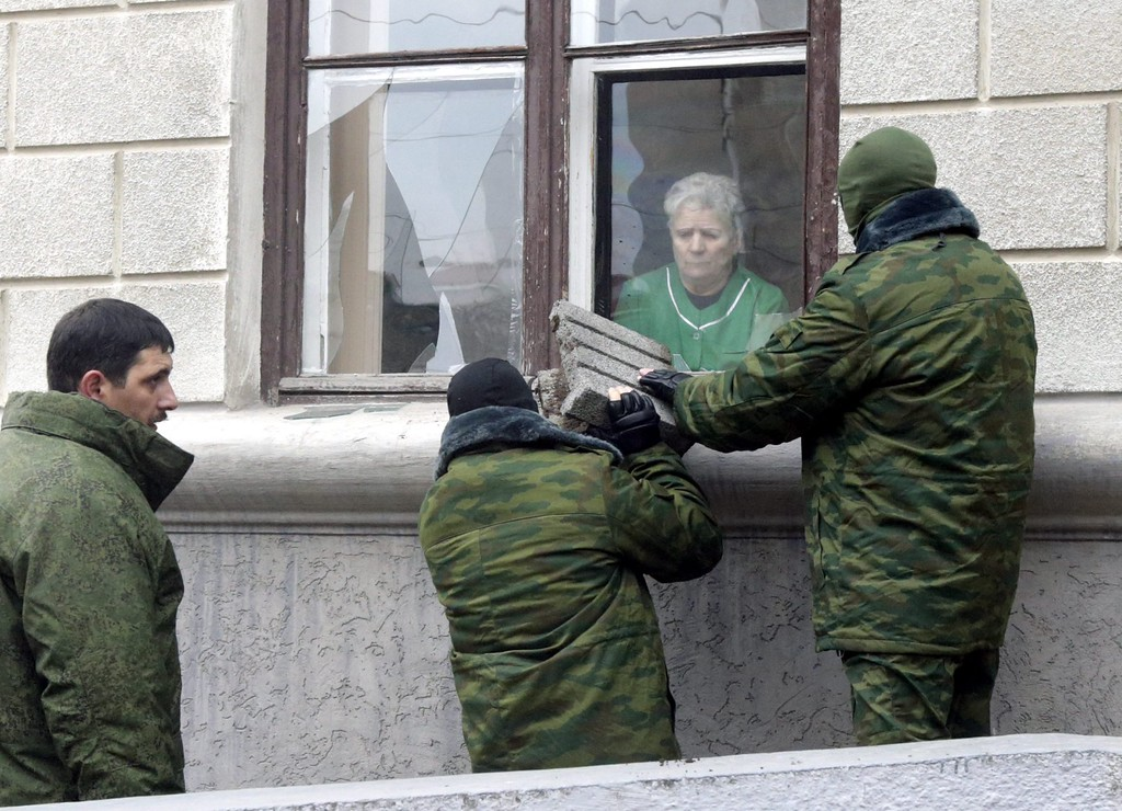 . Group of pro-Russia activists take over the control of trade union building in Simferopol, Ukraine, 01 March 2014. Unidentified armed men, described by Interior Minister Arsen Avakov as Russian naval forces, took control   28 February, of the airports in Simferopol and near the port of Sevastapol where the Russian Black Sea Fleet has a base.  Meanwhile the Russian senate has endorsed President Putin\'s requestto use armed forces against Ukraine.  EPA/MAXIM SHIPENKOV