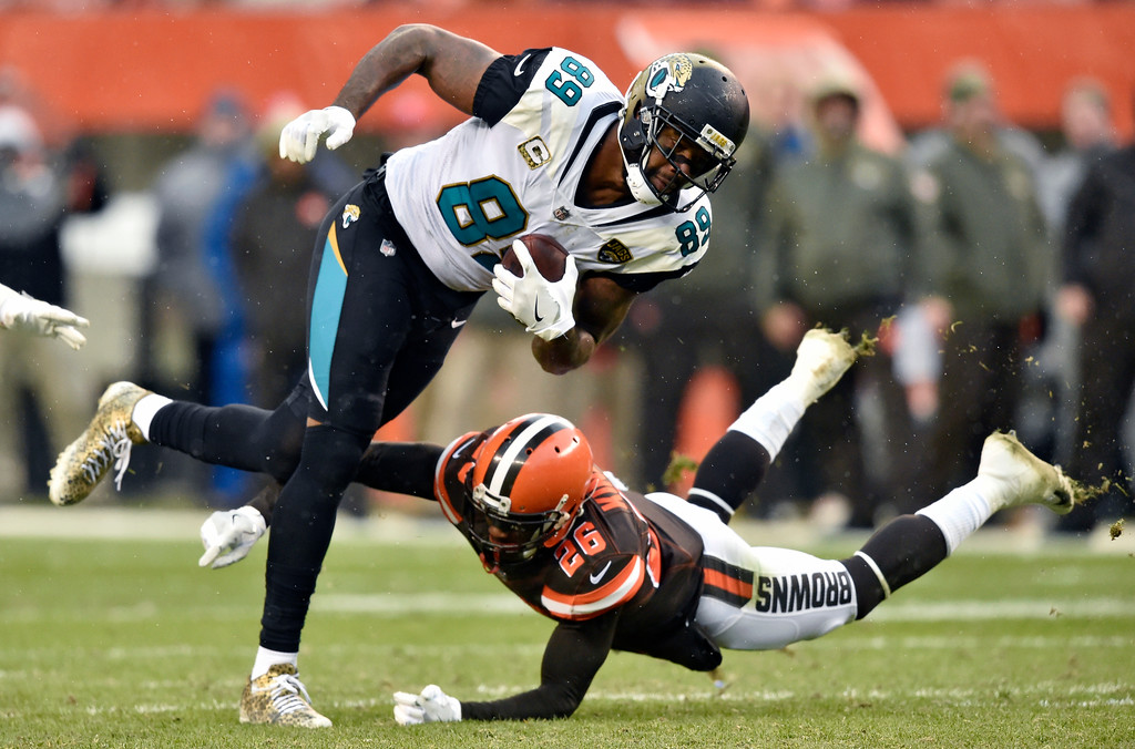 . Jacksonville Jaguars tight end Marcedes Lewis (89) is tackled by Cleveland Browns strong safety Derrick Kindred (26) in the first half of an NFL football game, Sunday, Nov. 19, 2017, in Cleveland. (AP Photo/David Richard)