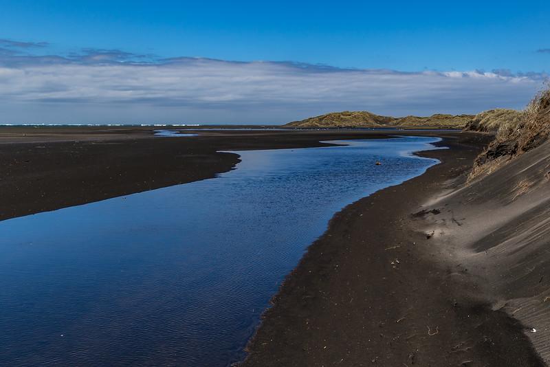 Zufluss ins Meer durch den schwarzen Sand