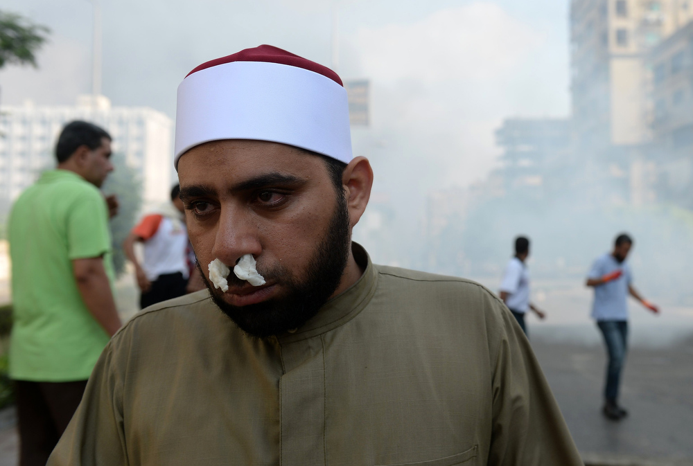 . Supporters of Egypt\'s ousted president Mohamed Morsi and members of the Muslim Brotherhood run from tear gas smoke shot by police to disperse a pro-Morsi protest camp, on August 14, 2013 near Cairo\'s Rabaa al-Adawiya mosque . Egypt\'s Muslim Brotherhood said at least 250 people were killed and over 5,000 injured in a police crackdown on two major protest camps held by supporters of ousted president Mohamed Morsi.  KHALED DESOUKI/AFP/Getty Images