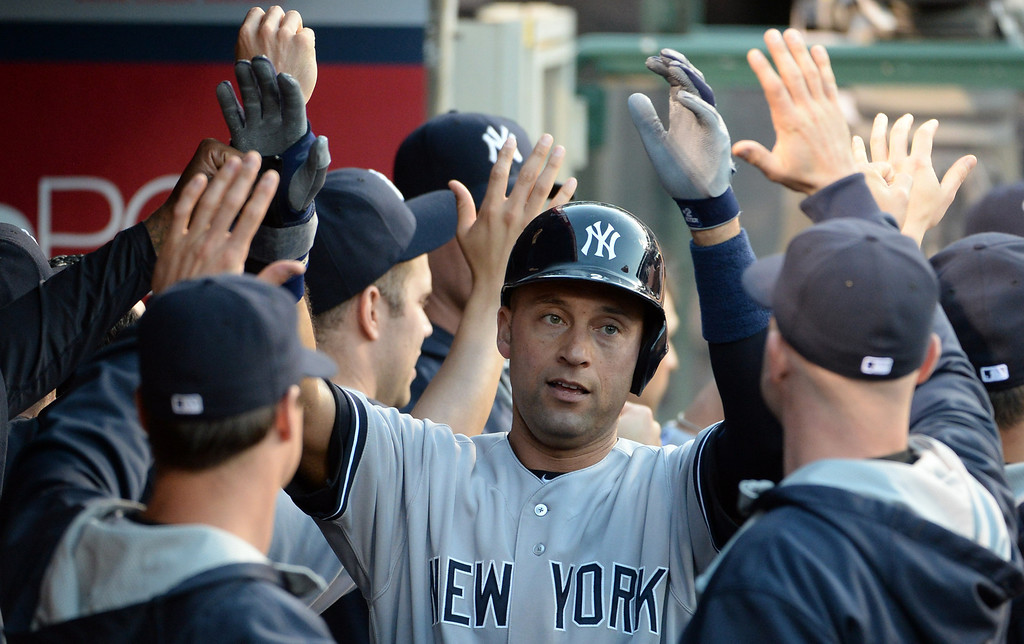 . New York Yankees\' Derek Jeter high fives teammates after scoring on a double by Mark Teixeira (not picture) in the first inning of a baseball game against the Los Angeles Angels at Anaheim Stadium in Anaheim, Calif., on Wednesday, May 7, 2014.  (Keith Birmingham Pasadena Star-News)