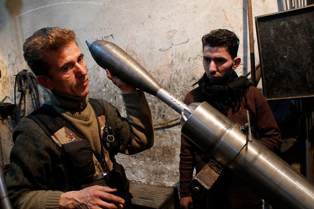 . A Free Syrian Army fighter holds an improvised mortar shell inside a factory which previously manufactured steel and iron in Aleppo February 18, 2013. REUTERS/Hamid Khatib