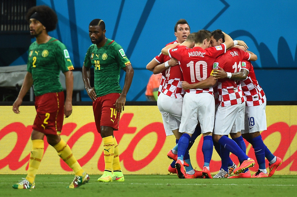 . Croatian players (R) led by Croatia\'s midfielder Luka Modric (C/10#) celebrate their first goal as Cameroon defender Benoit Assou-Ekotto (L) and defender Aurelien Chedjou (2L) look on during the Group A football match between Cameroon and Croatia at The Amazonia Arena in Manaus on June 18, 2014, during the 2014 FIFA World Cup.  JAVIER SORIANO/AFP/Getty Images