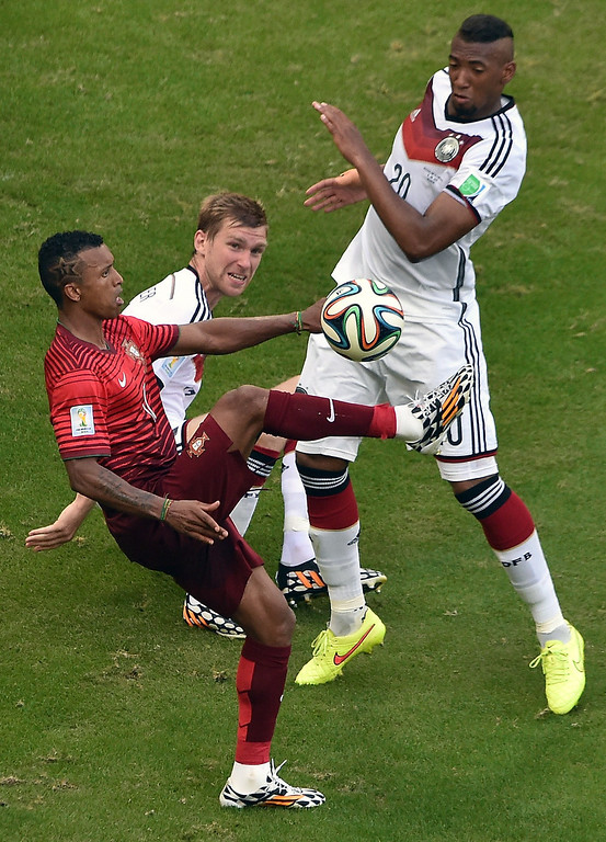 . Portugal\'s forward Nani (L) vies with Germany\'s defender Per Mertesacker (C) and Germany\'s defender Jerome Boateng during the Group G football match between Germany and Portugal at the Fonte Nova Arena in Salvador during the 2014 FIFA World Cup on June 16, 2014.  AFP PHOTO / DIMITAR DILKOFF/AFP/Getty Images