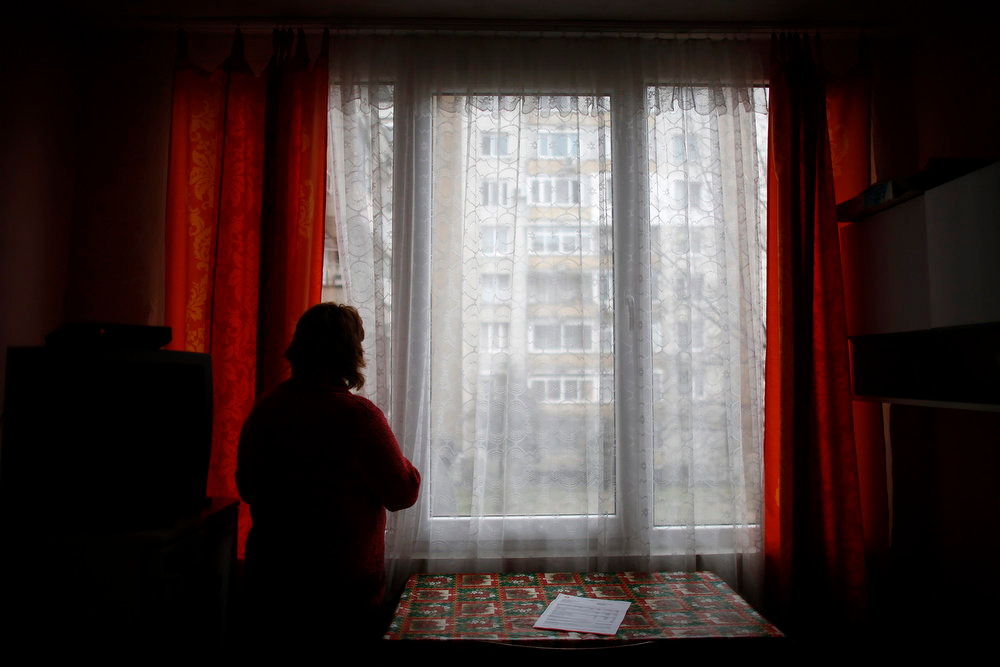 . Sirma Antonova looks out of the window in her apartment in the town of Blagoevgrad, west of Sofia February 22, 2013. Bulgaria\'s government has bowed to popular anger over high electricity prices and poor governance, but the spirit of protest in struggling towns like Blagoevgrad has not been quenched. Antonova\'s pension and benefits covered barely half of her December electricity bill of 270 levs ($180). A widow who lives in a two-room apartment with her two children, she has been unemployed since 2008.      REUTERS/Stoyan Nenov