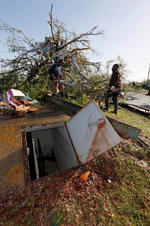 . Workers cut a tree behind an open storm shelter in Louisville, Miss., Tuesday, April 29, 2014.  (AP Photo/Rogelio V. Solis)