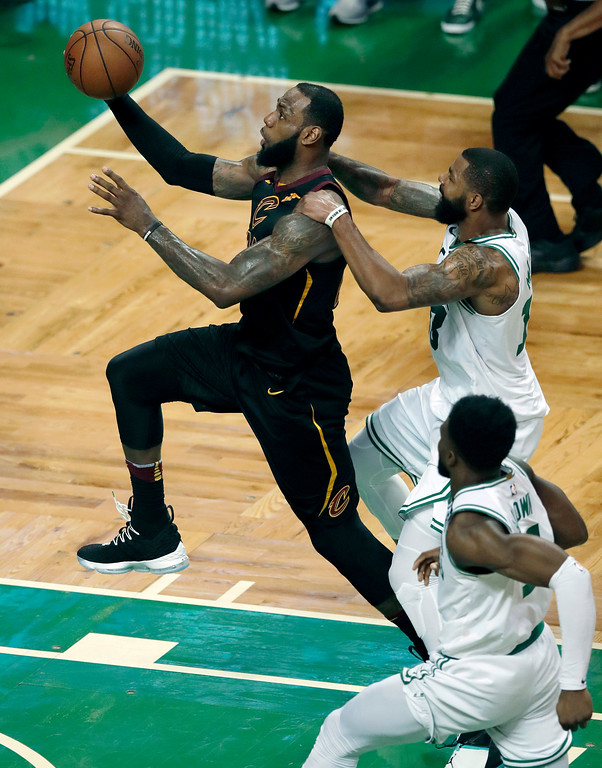 . Boston Celtics forward Marcus Morris, right, tries to slow Cleveland Cavaliers forward LeBron James as he drives to the basket during the second half in Game 7 of the NBA basketball Eastern Conference finals, Sunday, May 27, 2018, in Boston. (AP Photo/Charles Krupa)