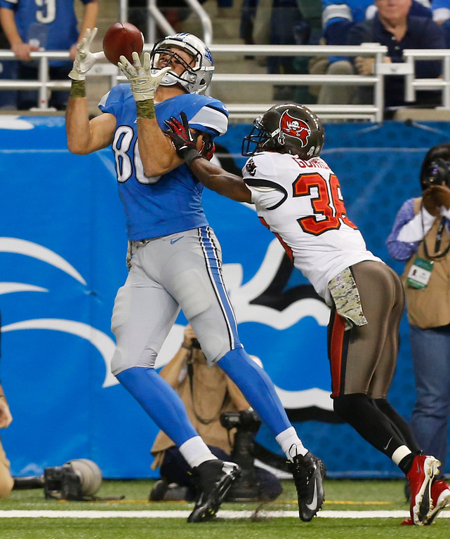 . Detroit Lions tight end Joseph Fauria (80), defended by Tampa Bay Buccaneers free safety Dashon Goldson (38), catches a 10-yard reception for a touchdown during the first half of an NFL football game in Detroit, Sunday, Nov. 24, 2013. (AP Photo/Paul Sancya)