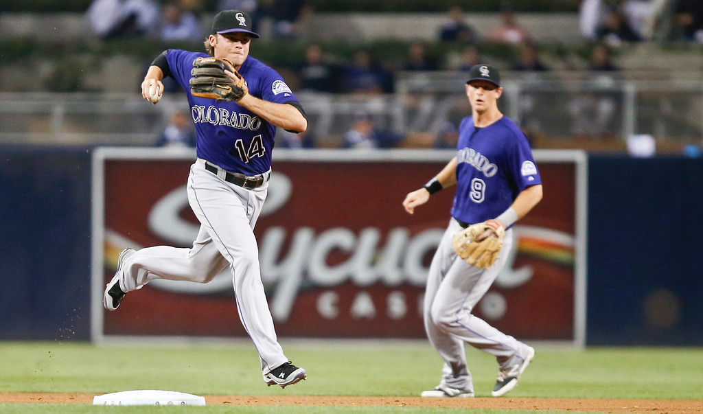 . Colorado Rockies shortstop Josh Rutledge fires a throw to first after fielding a slow bouncer up the middle hit by San Diego Padres\' Yangervis Solarte during the first  inning of a baseball game Monday, Sept. 22, 2014, in San Diego.  Rutledge got the out at first.  (AP Photo/Lenny Ignelzi)