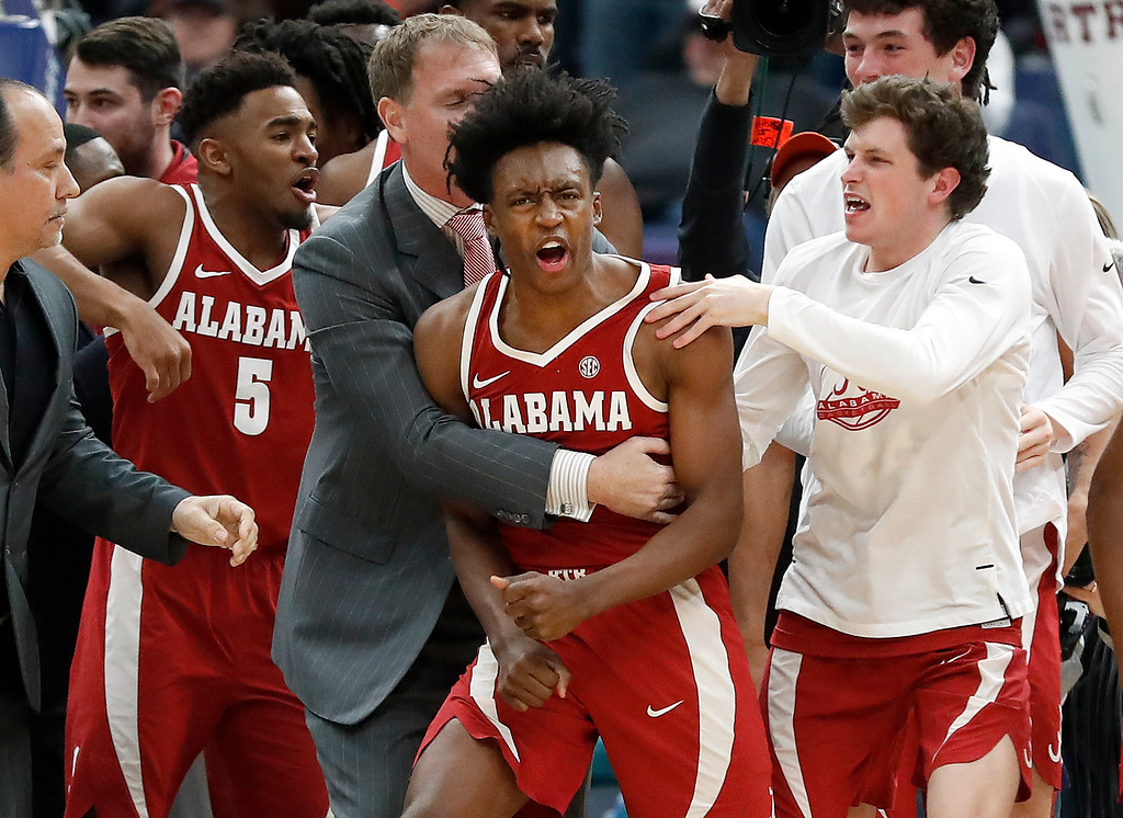 . Alabama\'s Collin Sexton, center, is congratulated by teammates after making a game-winning basket at the buzzer to defeat Texas A&M 71-70 in an NCAA college basketball game at the Southeastern Conference tournament Thursday, March 8, 2018, in St. Louis. (AP Photo/Jeff Roberson)