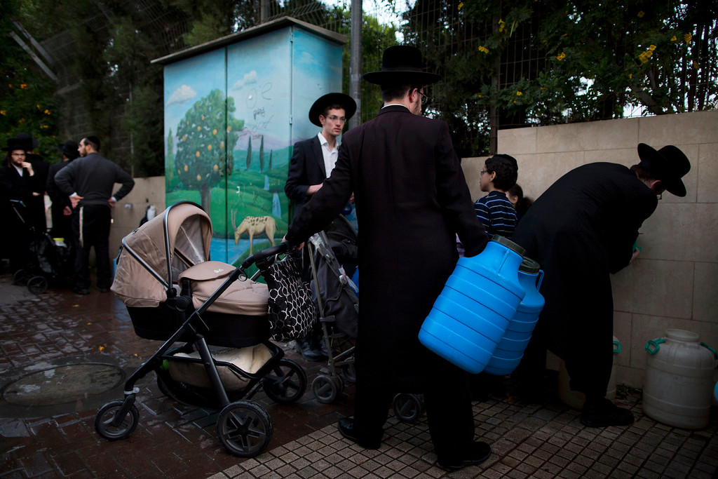 . Ultra-Orthodox Jewish men gather to collect water from a water tower to make matza, a traditional handmade Passover unleavened bread, in the ultra Orthodox Jewish town of Bnei Brak, Israel,  Thursday, April 14, 2016.  Jews are forbidden to eat leavened foodstuffs during the Passover holiday. Passover celebrates the biblical story of the Israelites\' escape from slavery and exodus from Egypt. (AP Photo/Oded Balilty)