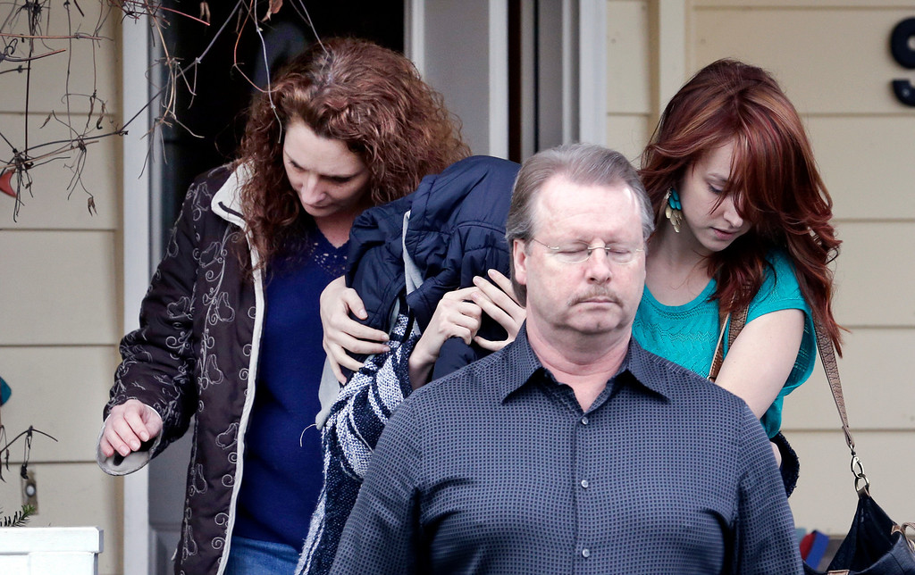 """. A woman believed to be Amanda Knox, center left, is hidden under a jacket while being escorted from her mother\'s home to a car by family members Thursday, Jan. 30, 2014, in Seattle. Amanda Knox says she is frightened and saddened by her \""""unjust\"""" murder conviction in the death of her British roommate Meredith Kercher. Knox\'s lawyers have vowed to appeal to Italy\'s highest court. In a statement issued from Seattle on Thursday after her conviction was upheld, Knox blamed overzealous prosecutors and a \""""prejudiced and narrow-minded investigation\"""" for what she called a perversion of justice and wrongful conviction. (AP Photo)"""