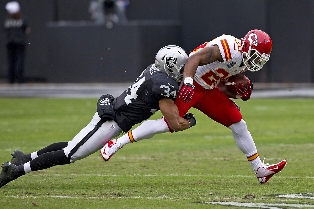 Description of . Running back Shaun Draughn #20 of the Kansas City Chiefs is tackled by strong safety Mike Mitchell #34 of the Oakland Raiders during the first quarter at O.co Coliseum on December 16, 2012 in Oakland, California.  (Photo by Jason O. Watson/Getty Images)