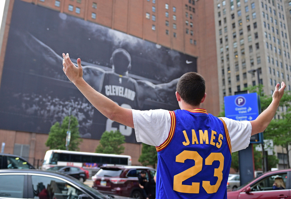 . Cleveland Cavaliers fan Jordan Phillips poses for a photo in front of a poster featuring Cleveland Cavaliers forward LeBron James, before Game 4 of the basketball\'s NBA Finals between the Cavaliers and the Golden State Warriors, Friday, June 9, 2017, in Cleveland. (AP Photo/David Dermer)