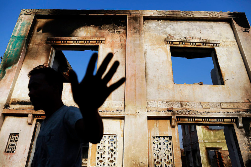 . A man reacts toward the photographer as he collects bricks from burnt Muslim homes in Meikhtila April 25, 2013. In Myanmar\'s central heartlands, justice and security is elusive for thousands of Muslims who lost their homes in a deadly rampage by Buddhist mobs in March. Many are detained in prison-like camps, unable to return to neighborhoods and businesses razed in four days of violence in Meikhtila that killed at least 43 people, most of them Muslims, displaced nearly 13,000, and touched off a wave of anti-Muslim unrest fueled by radical Buddhist monks. Picture taken April 25, 2013.   REUTERS/Damir Sagolj