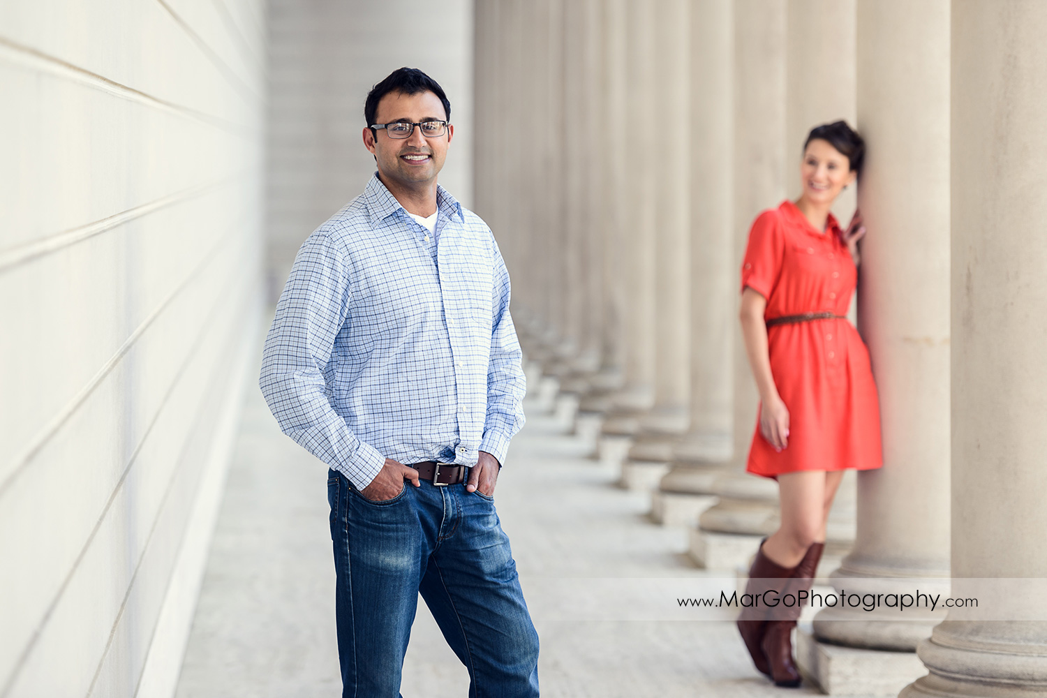man in blue shirt standing in front of woman in red dress between white wall and columns during engagement session at San Francisco Legion of Honor
