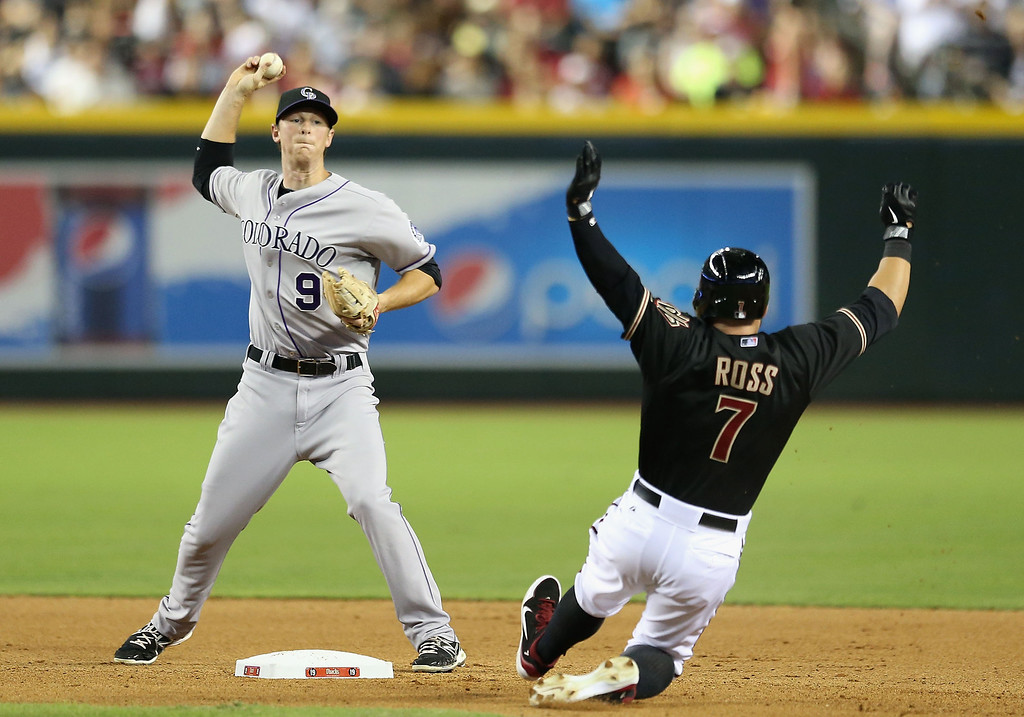 . PHOENIX, AZ - JULY 05:  Infielder DJ LeMahieu #9 of the Colorado Rockies throws over the sliding Cody Ross #7 of the Arizona Diamondbacks to compete a double play during the fourth inning of the MLB game at Chase Field on July 5, 2013 in Phoenix, Arizona.  (Photo by Christian Petersen/Getty Images)