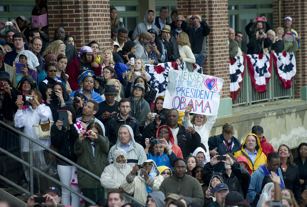 . People watch as US President Barack Obama greets people after speaking about rebuilding efforts following last year\'s Hurricane Sandy at the Asbury Park Convention Hall in Asbury Park, New Jersey, on May 28, 2013. AFP PHOTO / Saul LOEB/AFP/Getty Images