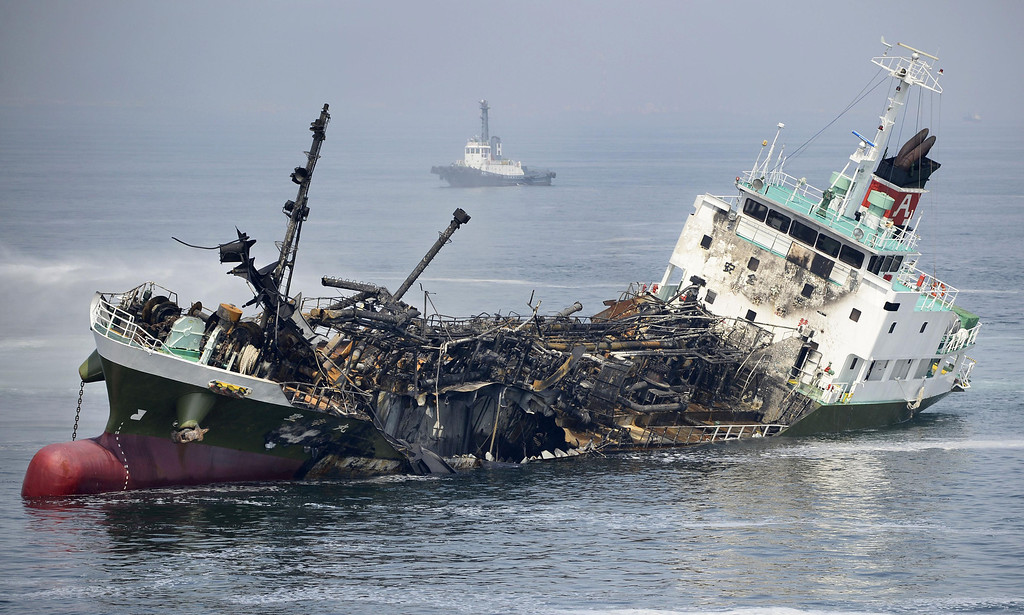 . The Shoko Maru, a 998-ton tanker, gutted by fire tilts after it exploded in waters off Himeji port, western Japan, Thursday, May 29, 2014. Japan Coast Guard said the Japanese oil tanker exploded Thursday, leaving one of the eight people aboard missing. (AP Photo/Kyodo News)