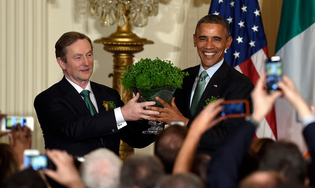 . President Barack Obama, right, and Irish Prime Minister Enda Kenny, left, hold up a bowl of shamrocks during a reception in the East Room of the White House in Washington, Tuesday, March 17, 2015. Obama is celebrating his seventh St. Patrick\'s Day in the White House. (AP Photo/Susan Walsh)