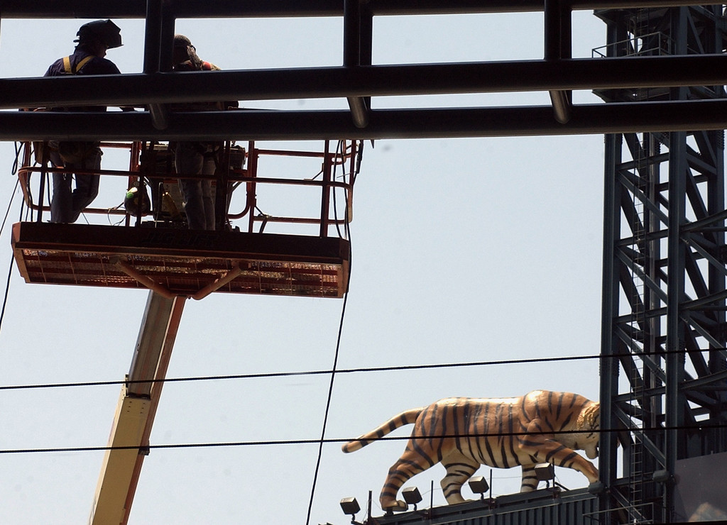 . A Detroit Tiger from Comerica park looms in the background as constructions workers work on the glass framing in the main plaza area at the new Ford Field, future site of the NFL Detroit Lions in downtown Detroit.