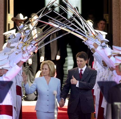 Description of . FILE - In this Jan. 21, 2003, file photo Texas Gov. Rick Perry, with his wife Anita, walks under the Ross Volunteers saber arch during Perry's inauguration in Austin, Texas.  Perry announced Monday, July 8, 2013, that he would not seek re-election as Texas governor next year.  (AP Photo/Eric Gay, File)