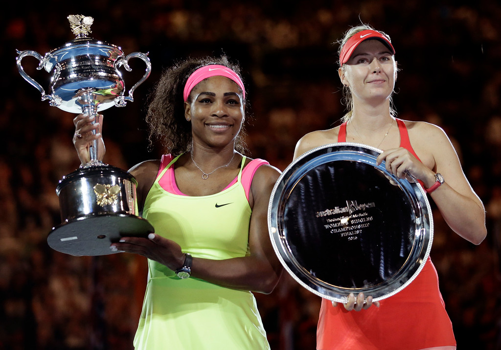 . Serena Williams of the U.S., left,  holds the trophy with runner-up Maria Sharapova of Russia in the women\'s singles final at the Australian Open tennis championship in Melbourne, Australia, Saturday, Jan. 31, 2015. (AP Photo/Bernat Armangue)