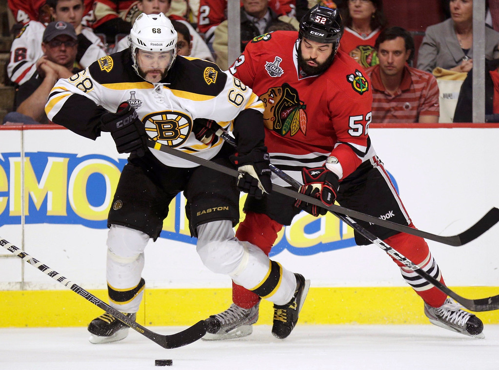. Boston Bruins right wing Jaromir Jagr (68) is checked by Chicago Blackhawks left wing Brandon Bollig (52) in double-overtime during Game 1 of their NHL Stanley Cup Finals hockey series in Chicago, Illinois, June 12, 2013.  REUTERS/John Gress