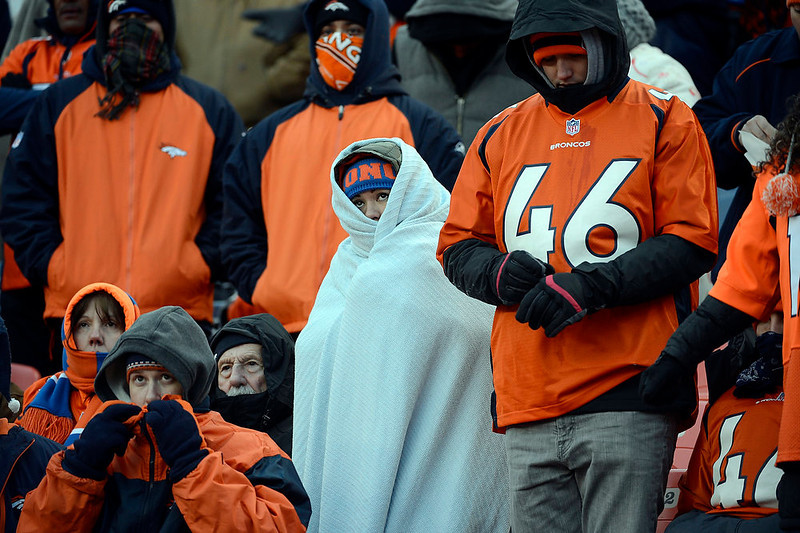. Broncos fans try to keep warm while watching their team play during the first half.  The Denver Broncos vs Baltimore Ravens AFC Divisional playoff game at Sports Authority Field Saturday January 12, 2013. (Photo by Tim Rasmussen,/The Denver Post)