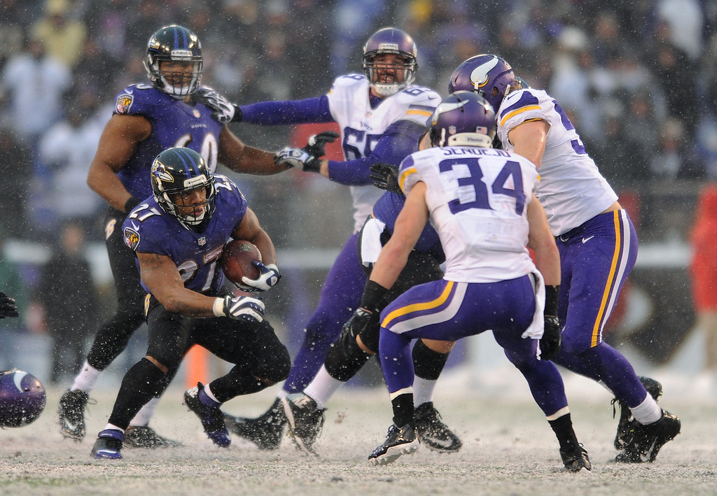 . Baltimore Ravens running back Ray Rice, front left, rushes around Minnesota Vikings free safety Andrew Sendejo (34) in the second half of an NFL football game on Sunday, Dec. 8, 2013, in Baltimore. (AP Photo/Gail Burton)
