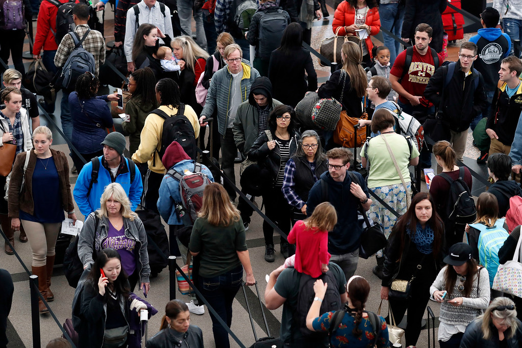 . Travelers crowd at a security checkpoint at Denver International Airport early Wednesday, Nov. 23, 2016, in Denver. Travelers are criss-crossing the country Wednesday, clogging airport terminals in a rush to reach their Thanksgiving Day destinations. (AP Photo/David Zalubowski)