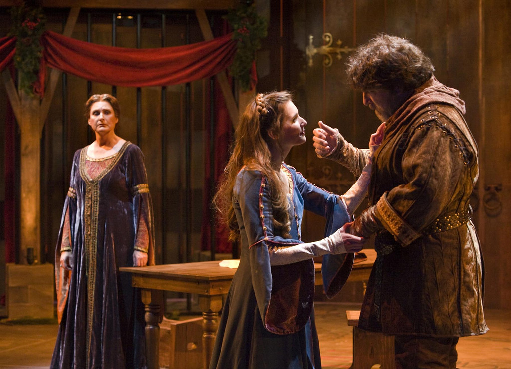 ". Eleanor of Aquitaine (Kandis Chappell) watches her husband, King Henry II (Marco Barricelli), and his mistress, Alais Capet (Mairin Lee) in the Shakespeare Santa Cruz production of ""The Lion In Winter.\"" (Photo courtesy of RR Jones)."
