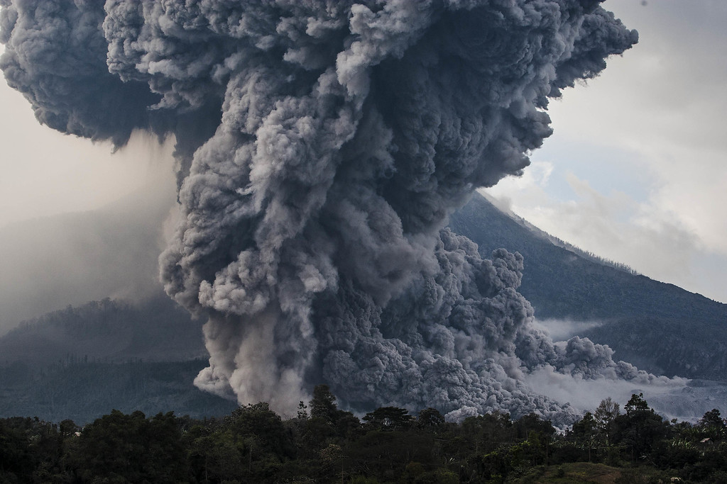 . Mount Sinabung spews pyroclastic smoke, seen from Tiga Pancur village on October 13, 2014 in Berastagi, Karo district, North Sumatra, Indonesia. Mount Sinabung, which has lain dormant for over 400 years, has been intermittently erupting since September 15 last year, killing 15 people and forcing hundreds to flee their homes. According to The National Disaster Mitigation Agency, more than 3,000 residents are still displaced. (Photo by Ulet Ifansasti/Getty Images)