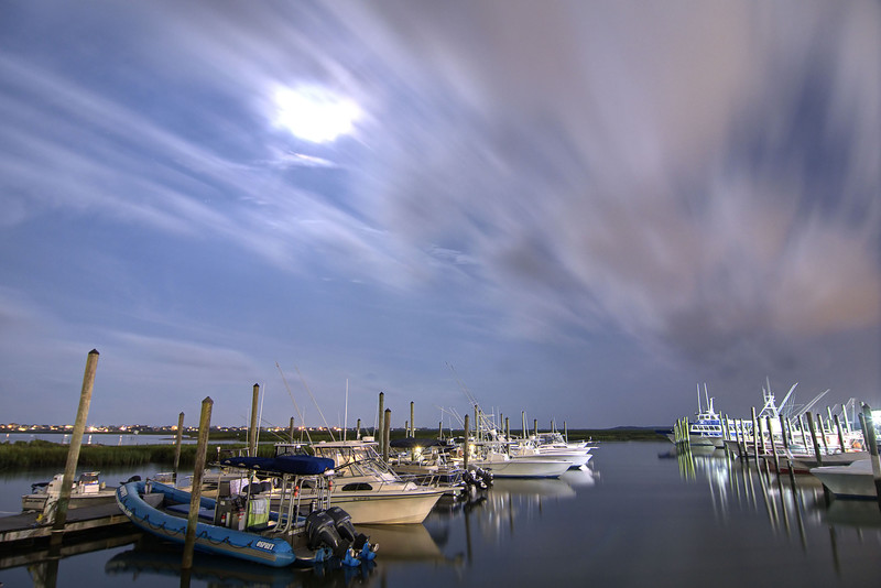 A full moon shines through partly cloudy skies over the Marshwalk in Murrells Inlet, SC on Thursday, July 10, 2014. Copyright 2014 Jason Barnette  The Marshwalk is a long wooden boardwalk that meanders along several restaurants and across a fishing pier on the marshes, providing stunning views and loads of options for outdoor recreation on the water.