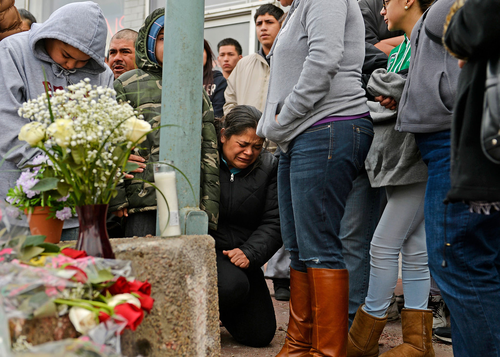 . Blanca Palomino falls to her knees as she gathers with friends and family at the corner of East Colfax Avenue and Dayton Street in Aurora where her older son, Juan Carlos Dominguez-Palomino, was killed earlier in a fatal crash, Monday, March 24, 2014. (Photo by RJ Sangosti/The Denver Post)