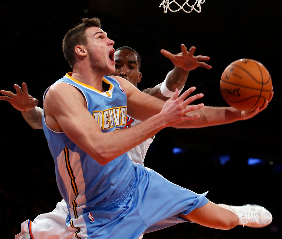 . Denver Nuggets\' Danilo Gallinari is fouled as he shoots against New York Knicks\' J.R. Smith during an NBA basketball game, Sunday, Dec. 9, 2012, in New York. New York beat Denver, 112-106. (AP Photo/Jason DeCrow)