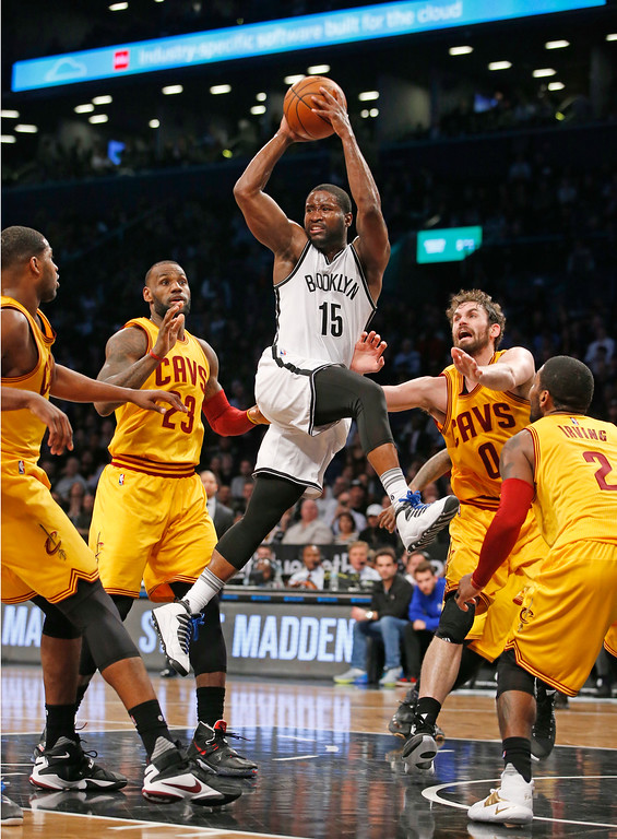 . Brooklyn Nets guard Donald Sloan (15) look to pass to the perimeter as Cleveland Cavaliers forwards LeBron James (23), Kevin Love (0) and Cavaliers guard Kyrie Irving (2) defend in the fourth quarter of an NBA basketball game, Thursday, March 24, 2016, in New York. The Nets beat the Cavaliers 104-95. (AP Photo/Kathy Willens)