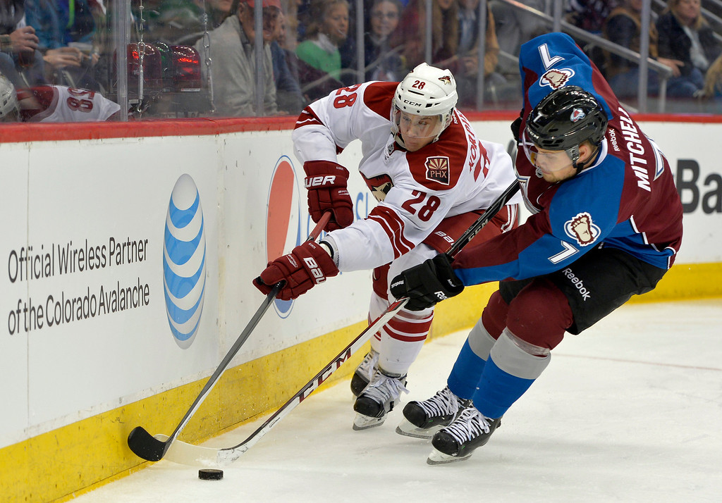 . Colorado Avalanche center John Mitchell (7) and Phoenix Coyotes left wing Lauri Korpikoski (28) chase the puck into the corner during the second period of an NHL hockey game on Friday, Feb. 28, 2014, in Denver. (AP Photo/Jack Dempsey)