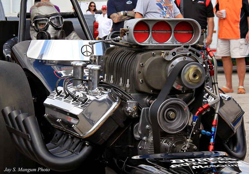 A supercharged, early model Chrysler hemi at the moment when it has nitro running through its veins. Over the years nothing else in drag racing has stirred the emotions of fans as much as this. The sights, scents, and thunderous vibrations of this engine, especially in full competitive attitude, are unforgettable.