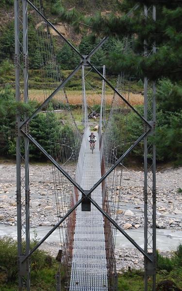 Scott coming across a suspension bridge.