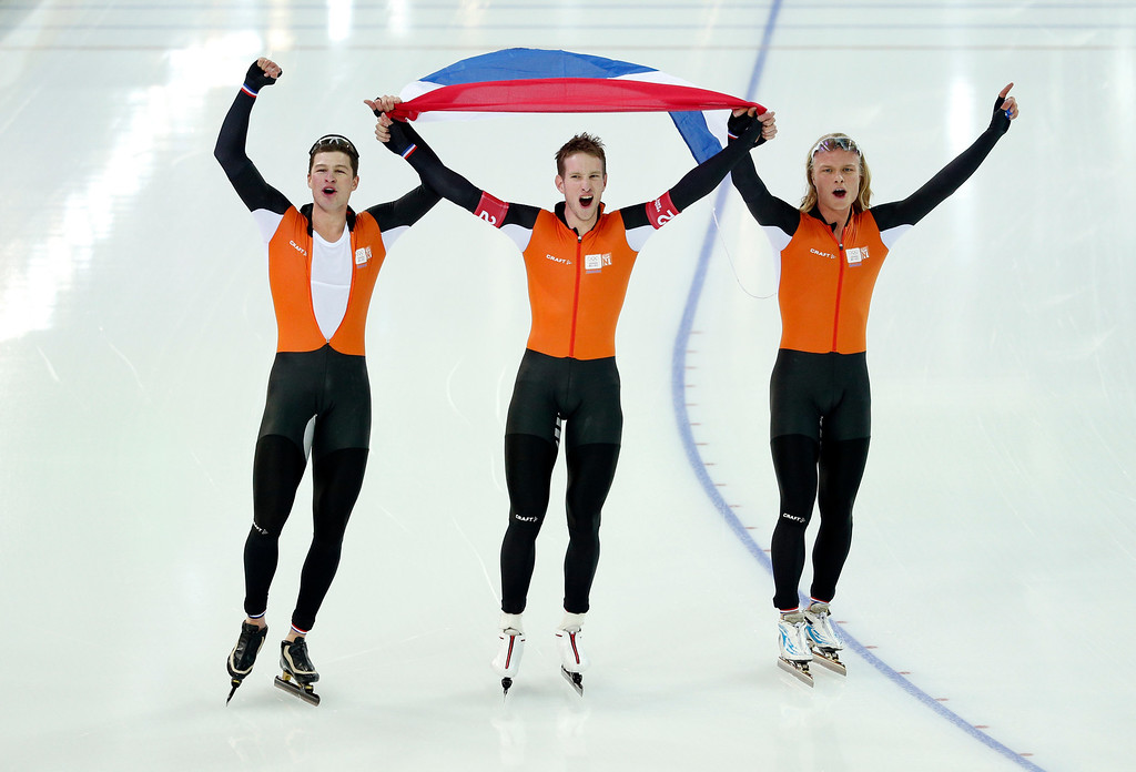 . Speedskaters from the Netherlands, left to right Sven Kramer, Jan Blokhuijsen and Koen Verweij hold their national flag and celebrate winning gold in the men\'s team pursuit at the Adler Arena Skating Center at the 2014 Winter Olympics, Saturday, Feb. 22, 2014, in Sochi, Russia. (AP Photo/Pavel Golovkin)