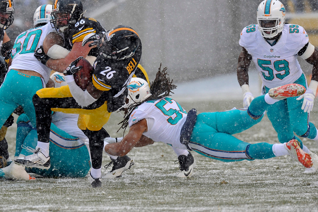 . Pittsburgh Steelers running back Le\'Veon Bell (26) spins away from Miami Dolphins outside linebacker Philip Wheeler (52)  during the first quarter of an NFL football game against the Miami Dolphins in Pittsburgh, Sunday, Dec. 8, 2013. (AP Photo/Don Wright)